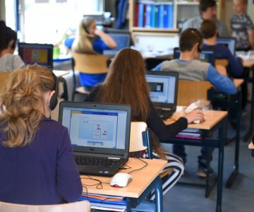 Schüler*innen in einer Klasse, die an Laptops arbeiten