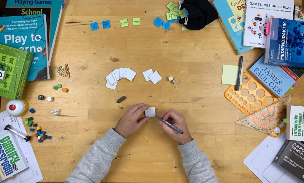 Hinweisbild zum Open Edu Game Jam mit einem Tisch von oben mit einem Gesellschaftsspiel