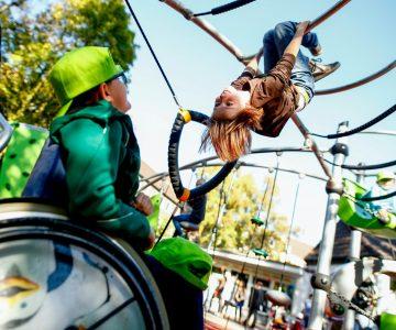 """Bild für das Lernmodul """"Inklusion"""" mit einem Spielplatz, auf dem ein Kind klettert und ein weiteres Kind im Rollstuhl dieses beobachtet"""