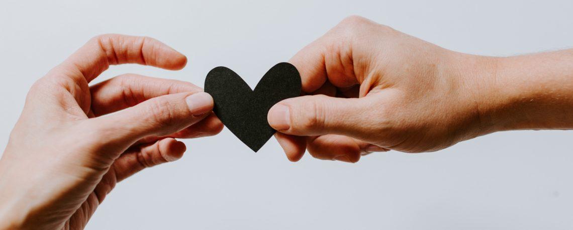Bild zweier Hände, die ein schwarzes Herz halten als EInstieg in das Lernmodul trauerarbeit in der Schule